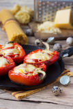 Red pepper stuffed with pasta and cheese. In pan on old wooden table Royalty Free Stock Photo