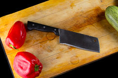 Red pepper and vegetable marrow with knife on a wooden board Royalty Free Stock Photography