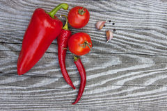 Red pepper and vegetables on wooden texture. Spices Royalty Free Stock Photography
