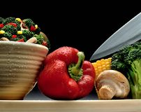 RED PEPPER WITH VEGGIES MUSHROOM CORN BROCCOLI AND KNIFE. Various veggies and bowl on tabletop still life Royalty Free Stock Photos