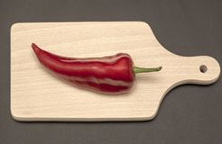Red pepper on wood cutting board. Vegetarian diet Royalty Free Stock Photos