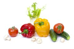 Red pepper with yellow pepper and tomatoes on a white background. Cucumbers with peppers and tomatoes. Stock Photo