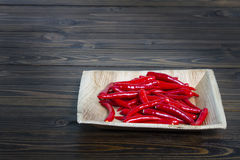 Red peppers in the bark bowl Royalty Free Stock Photos
