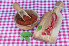 Red  peppers dried, cut and crushed. Red  peppers cut and crushed in wooden bowl on picnic cloth Stock Image