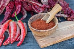 Red  peppers dried, cut and crushed. Red  peppers cut and crushed in wooden bowl on wooden background Stock Photo
