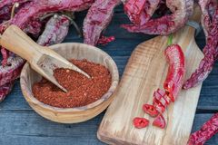 Red  peppers dried, cut and crushed. Red  peppers cut and crushed in wooden bowl on wooden background Stock Images