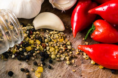Red peppers and garlic. Red Hot chili peppers with garlic and mixed spices on the wooden background Royalty Free Stock Photos