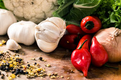 Red peppers and garlic. Red Hot chili peppers with garlic and mixed spices on the wooden background Stock Images