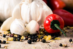 Red peppers and garlic. Red Hot chili peppers with garlic and mixed spices on the wooden background Royalty Free Stock Photography