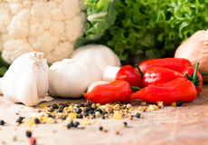 Red peppers and garlic. Red Hot chili peppers with garlic and mixed spices on the wooden background Royalty Free Stock Image