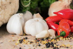 Red peppers and garlic. Red Hot chili peppers with garlic and mixed spices on the wooden background Stock Image