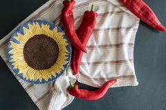 Red Peppers marry with a Stripped Cotton Cloth and a  Sunflower Bowl. Peppers with Sunflower Bowl on stripped towel Stock Photos