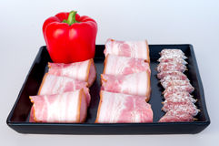 Red peppers with sausages and bacon Royalty Free Stock Photography