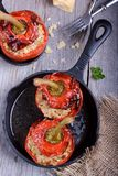 Red peppers stuffed with bulgur and meat. In cast-iron frying pan Stock Image