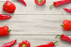 Red peppers on wooden kitchen desk. Free space in the middle for text or logo promotion.  royalty free stock photo