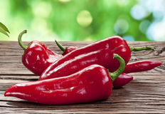 Red peppers on a wooden table. Stock Photos
