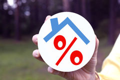 Red percent under the roof in a woman's hand Stock Photos