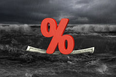 Red percentage on money boat with oncoming wave in dark Stock Photography
