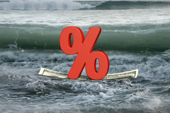 Red percentage sign on money boat floating in the ocean Stock Photo