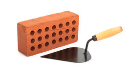 Red perforated ceramic brick and trowel isolated Royalty Free Stock Photo