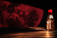 Red perfume bottle. Perfume bottle isolated on night scene background Stock Images
