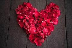Red petal roses shaped like a heart on wood background, Royalty Free Stock Images
