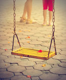 Red petal on yellow swing and cement floor in vintage color tone Stock Photo