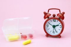 Red pharmaceutical pills, tablets and yellow capsules spilling out of daily pill box with red alarm clock. Medical conceptual phot Stock Images