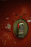 Red Phone. Public phone on a red graffiti painted wall Stock Photography