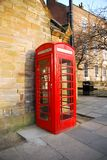 Red Phone Booth. A vibrant red english style phone booth against a stone building Stock Photo
