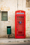 Red phone booth. In the background of an wall Royalty Free Stock Photo