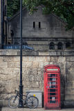Red phone booth and bicyle. Red phone booth an iconic symbol of British heritage and an old bicycle on the streets of oxford England Royalty Free Stock Photo