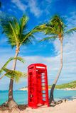 Beautiful landscape with a classic phone booth on the white sandy beach in Antigua royalty free stock images