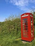 Red phone booth in England. A red, English telephone booth in nature Royalty Free Stock Photography
