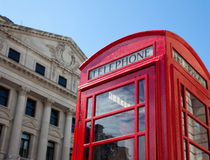 Red phone booth in London with historic buildings. Typical red phone booth in the City of London with historic buildings Royalty Free Stock Photos