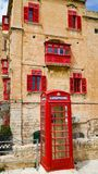Red phone booth and old balconies in the ancient city of Valletta, Malta. Red phone booth and old balconies in the ancient city of Valletta, Malta Royalty Free Stock Image