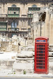 Red phone booth. A red phone booth at the Royal Opera House ruins in Valletta, Malta Stock Photo
