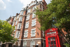 Red phone box in front of red brick apartments. Royalty Free Stock Photography