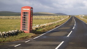 Red phone box at a road. A typical British red telephone box standing next to a road royalty free stock images