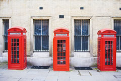 Red phone boxes. Three red phone boxes over grunge wall background royalty free stock images