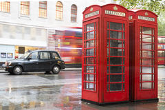 Red Phone cabines in London and vintage taxi.Rainy day. Stock Image