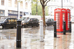 Red Phone cabines in London and vintage taxi.Rainy day. Stock Photo