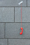 Red phone hanging down taped to a wall Royalty Free Stock Photography