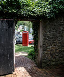 Red phone, open door and a stone wall. View of the Red phone booth through the open door Royalty Free Stock Image