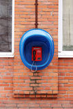 Red phone public apparatus protected blue booth on the brick wall of the house. Royalty Free Stock Photos