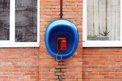 Red phone public apparatus protected blue booth on the brick wall of the house. Stock Images