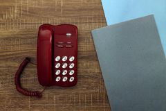 Red phone and stack of folders on a wooden table stock images