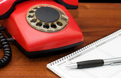 Red phone on a wooden table Royalty Free Stock Photo