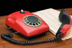 Red phone on a wooden table Stock Image