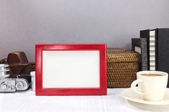 Red photo frame, old camera with leather cover, photo albums and Royalty Free Stock Image